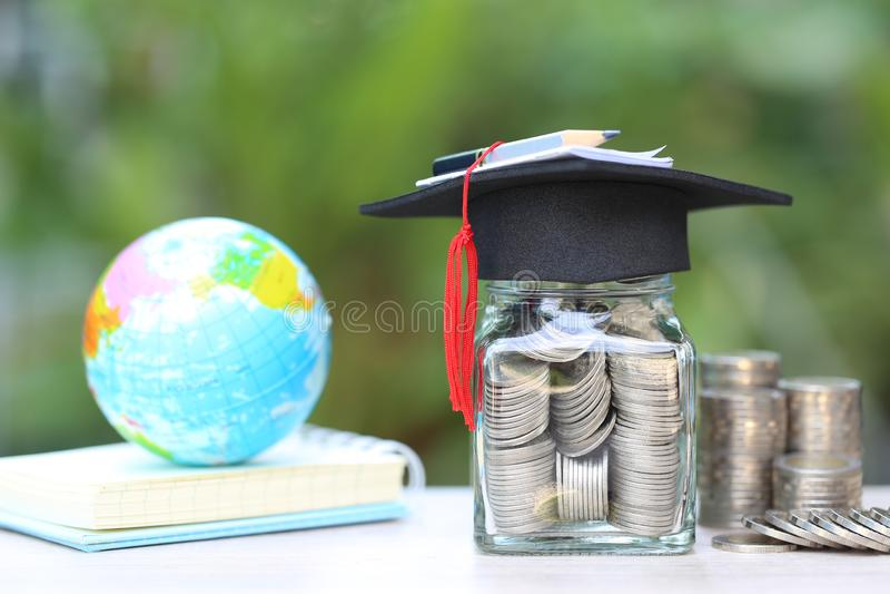 Sombrero de la graduaci?n en la botella de cristal y los libros en el fondo verde natural, dinero de ahorro para el concepto de l imágenes de archivo libres de regalías
