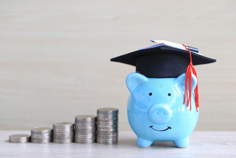 Sombrero de la graduaci?n en la hucha azul con la pila de dinero de las monedas en el fondo de madera, dinero de ahorro para el c fotografía de archivo libre de regalías