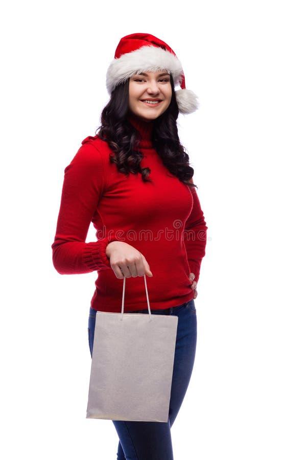sombrero de la Navidad de la mujer que lleva morena que sostiene el actual bolso con una cara feliz Aislado imagen de archivo