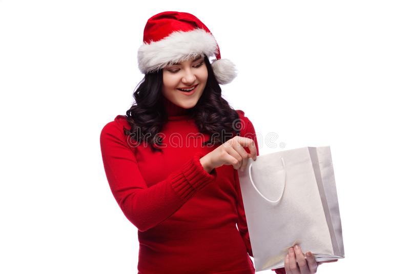 Sombrero de la Navidad de la mujer que lleva morena que sostiene el actual bolso con una cara sorprendida feliz Aislado foto de archivo