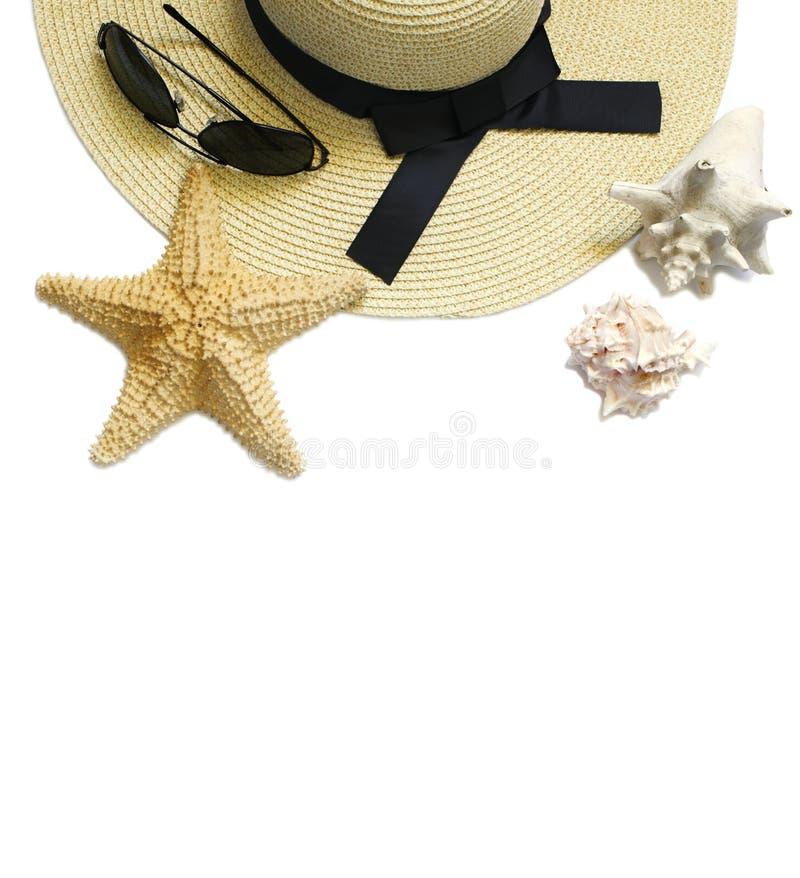 Sombrero de la paja de las mujeres, gafas de sol y conchas marinas aislados en el fondo blanco Composición puesta plana de la mod fotos de archivo