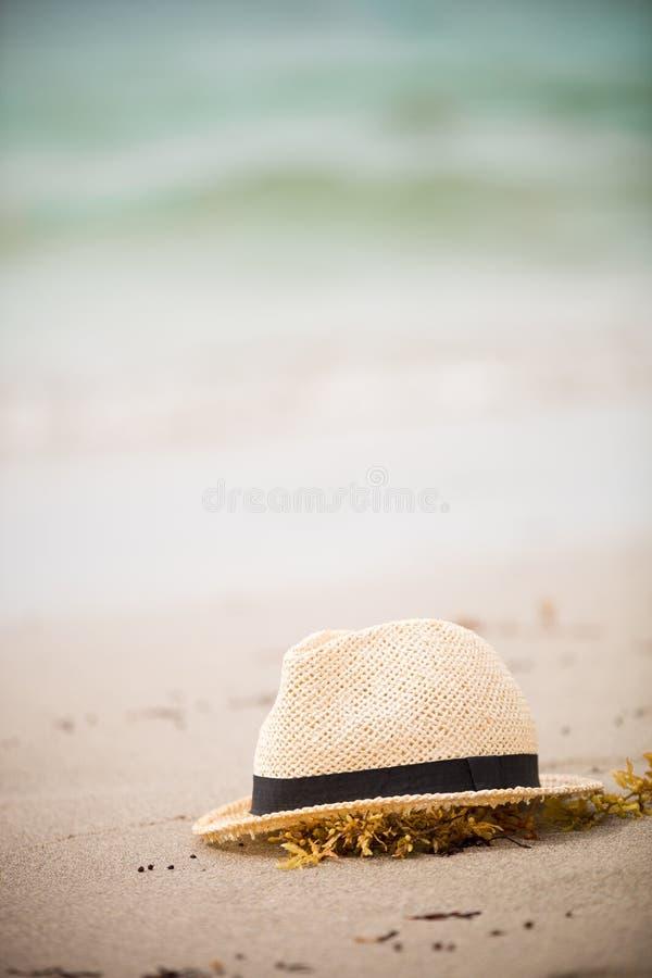Sombrero de paja agradable que pone en la arena Fondo hermoso de la playa del océano outdoors Tiempo de vacaciones Finales de las fotografía de archivo libre de regalías