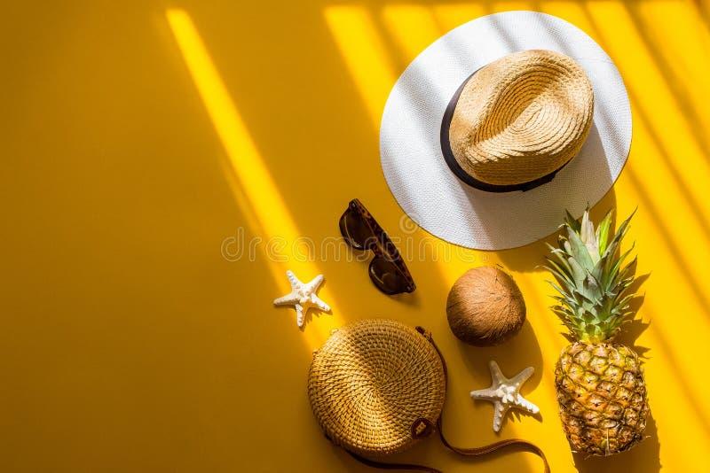 Sombrero de paja, bolso de bambú, gafas de sol, coco, piña, estrella de mar sobre el fondo amarillo, visión superior Moda del ver foto de archivo libre de regalías