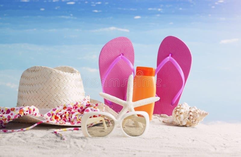 Sombrero de paja, bolso, vidrios de sol y chancletas en una playa tropical imágenes de archivo libres de regalías