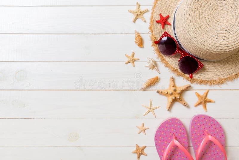 Sombrero de paja, chancletas rosadas, gafas de sol y estrellas de mar en un fondo de madera blanco concepto de las vacaciones de  fotos de archivo libres de regalías