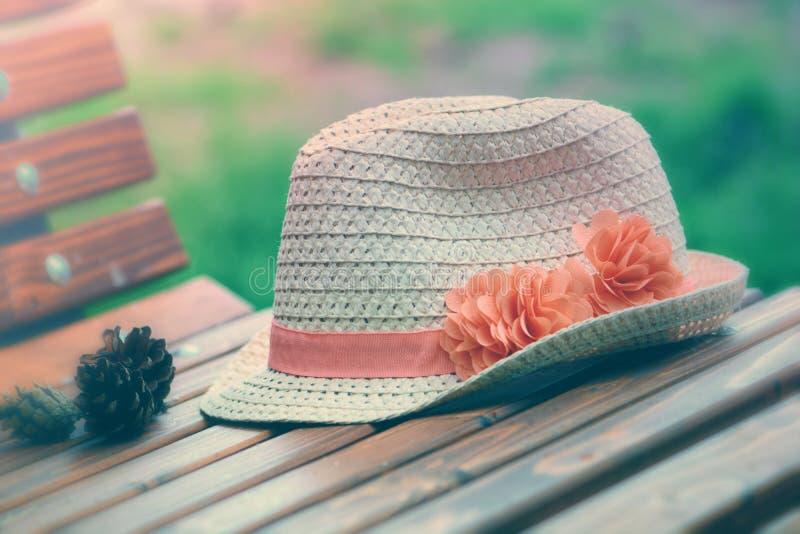Sombrero de paja clásico en un banco fotos de archivo