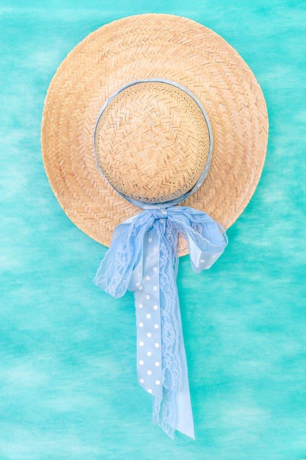 Sombrero de paja con la cinta azul en un fondo verde de la aguamarina fotografía de archivo