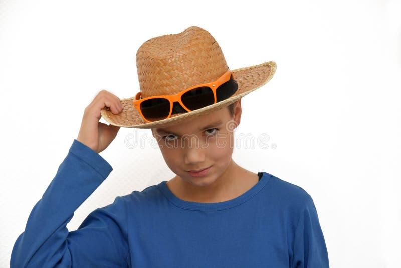 Sombrero de paja del muchacho que lleva imagen de archivo