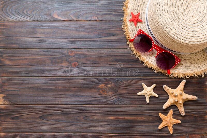 Sombrero de paja, gafas de sol y estrellas de mar en un fondo de madera oscuro concepto de las vacaciones de verano de la visi?n  fotos de archivo