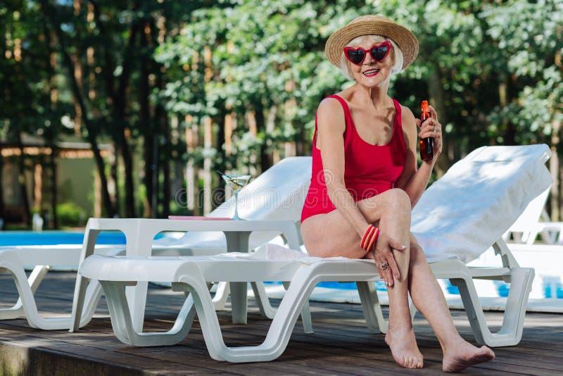 Sombrero de paja jubilado de emisión sano de la mujer que lleva que consigue bronceado fotos de archivo