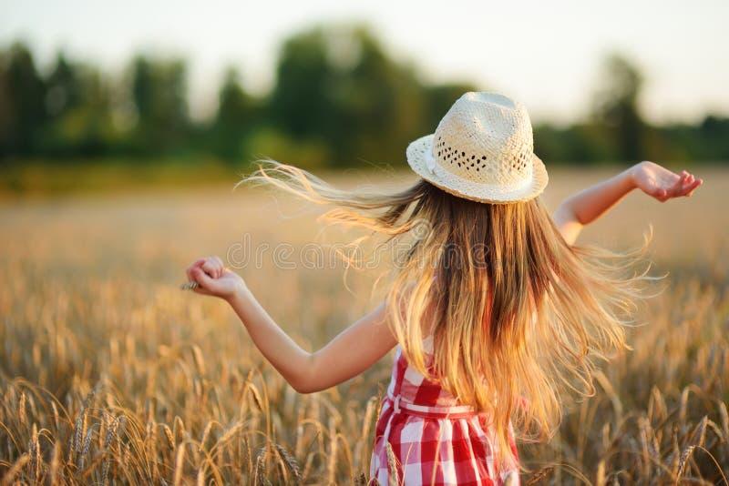 Sombrero de paja de la muchacha que lleva adorable que camina feliz en campo de trigo en la tarde caliente y soleada del verano foto de archivo libre de regalías