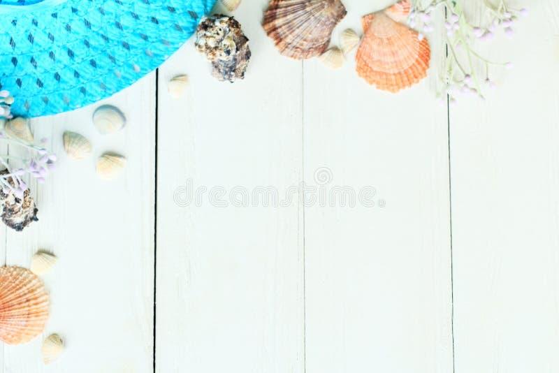 Sombrero de paja de playa y conchas marinas sobre un fondo de madera foto con lugar para texto foto de archivo libre de regalías
