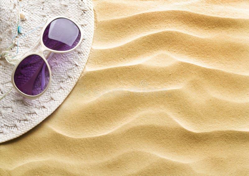 Sombrero de paja y gafas de sol en la arena de la playa imagen de archivo
