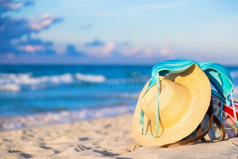 Sombrero de paja y traje de baño azul del sujetador del bikini con el bolso de la playa contra la playa del océano con el cielo a imagen de archivo