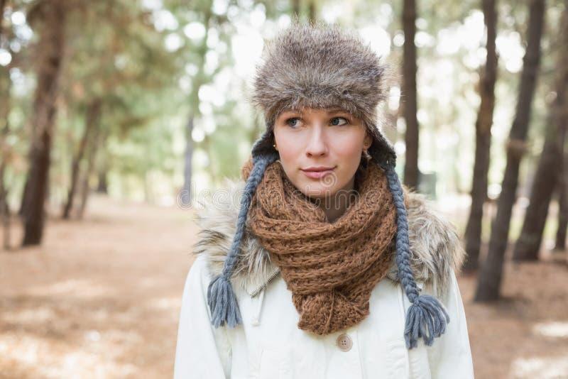Sombrero de piel de la mujer que lleva con la bufanda y la chaqueta de lana en bosque imagen de archivo libre de regalías