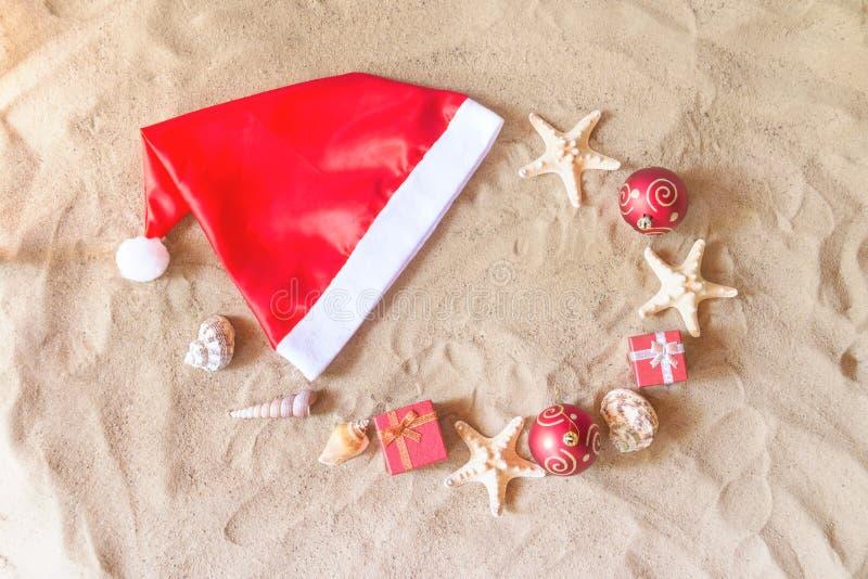 Sombrero de Santa Claus, bolas de la Navidad, regalos, conchas marinas y estrellas de mar foto de archivo