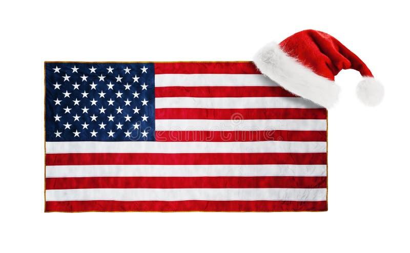 Sombrero de Santa Claus colgado en la bandera de los E.E.U.U. fotos de archivo