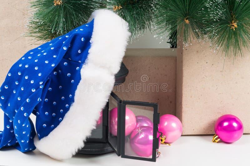 Sombrero de Santa Claus, y bolas rosadas, dispersadas debajo del árbol de navidad foto de archivo