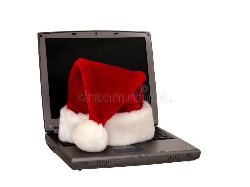 Sombrero de Santa que se sienta en una computadora portátil (1 de 3) fotografía de archivo libre de regalías