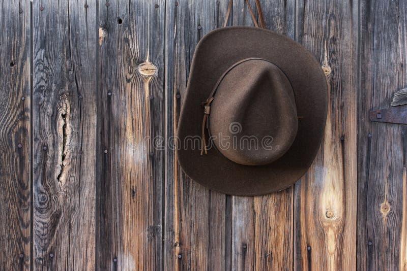 Sombrero de vaquero del fieltro en la pared del granero foto de archivo libre de regalías