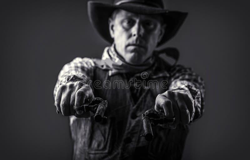 Sombrero de vaquero del hombre que lleva, arma Retrato de un vaquero Oeste, armas Retrato de un vaquero Bandido americano en la m foto de archivo libre de regalías