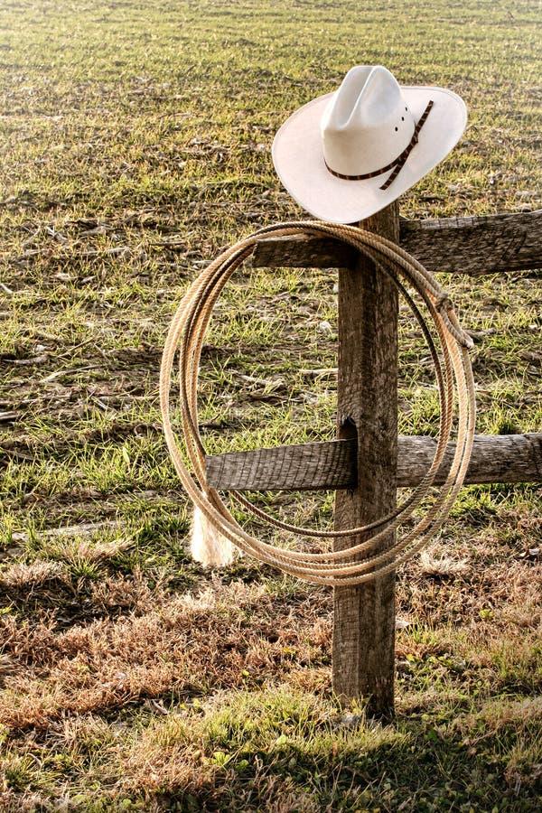Sombrero de vaquero del rodeo y lazo del oeste americanos en la cerca imagenes de archivo