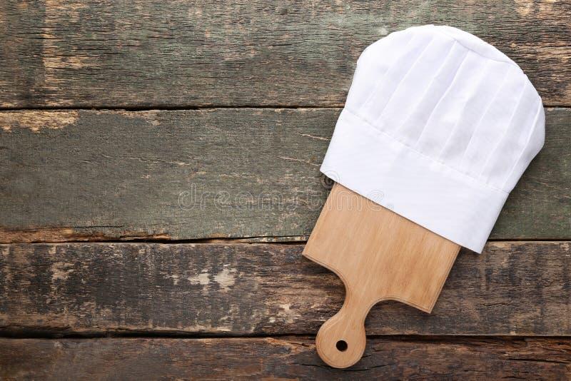 Sombrero del cocinero con la tabla de cortar foto de archivo