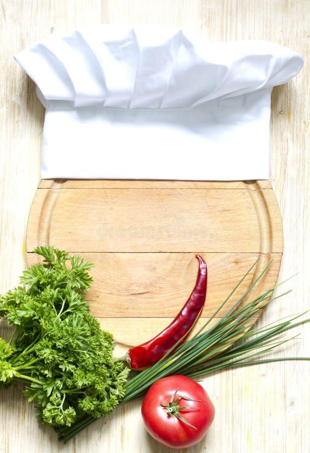 Sombrero del cocinero en concepto de la comida del extracto de la tabla de cortar imagen de archivo libre de regalías
