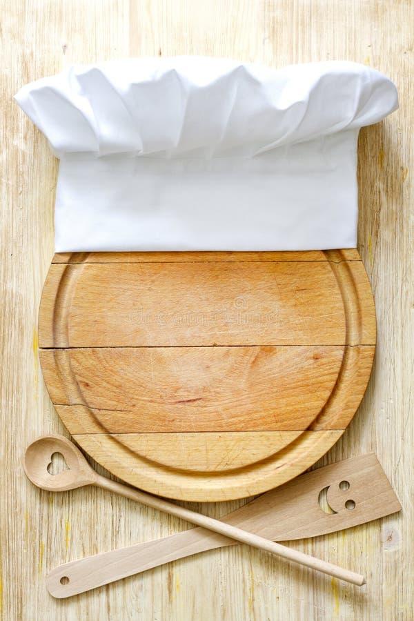 Sombrero del cocinero en concepto de la comida del extracto de la tabla de cortar imagenes de archivo