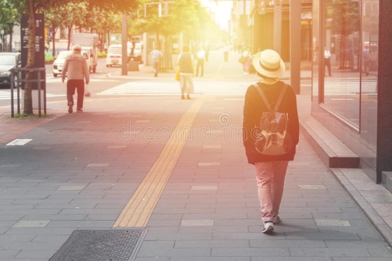 Sombrero del desgaste del viajero de la mujer y el caminar en la calle en la ciudad de Sapporo con luz del sol en el fondo en Jap fotografía de archivo