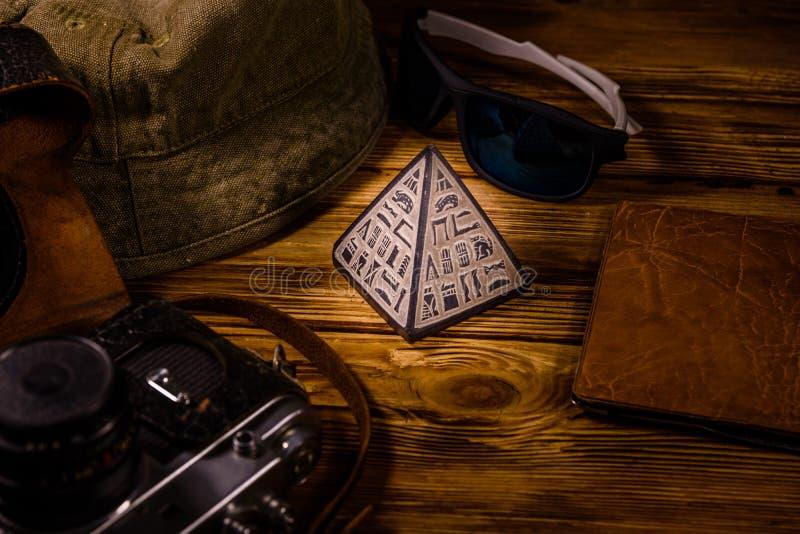 Sombrero del inconformista, c?mara del vintage, gafas de sol, pir?mide del recuerdo y pasaporte en un fondo de madera Recorrido a fotografía de archivo