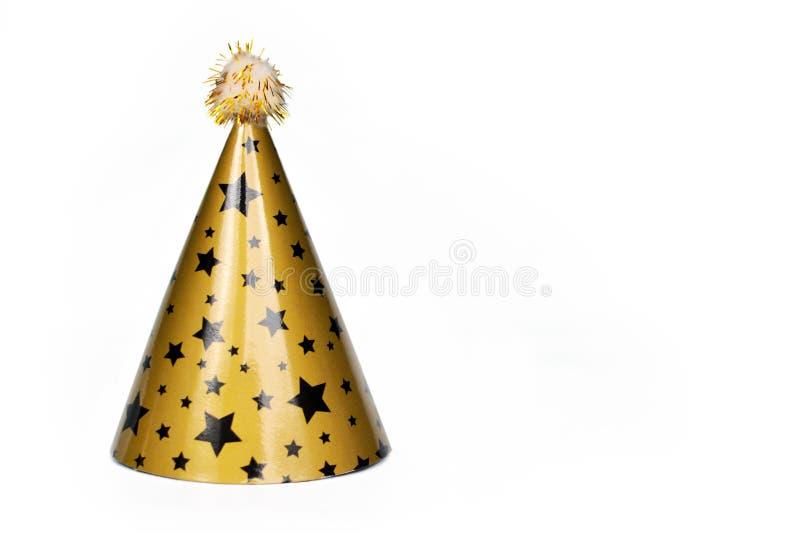 Sombrero del partido del oro con las estrellas negras y pompón aislado en el fondo blanco imagenes de archivo