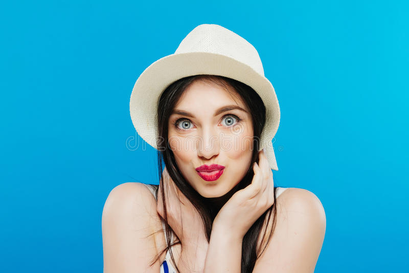 Sombrero del verano de la muchacha que lleva bastante Oscuro-cabelluda que presenta en estudio en fondo azul imagen de archivo libre de regalías