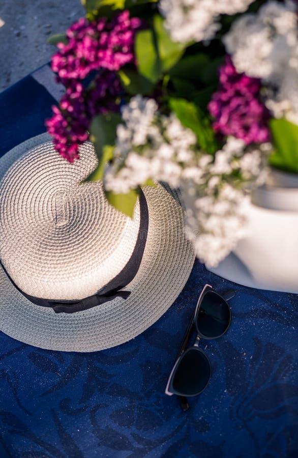Sombrero del verano de las mujeres con una cinta y un ramo de flores de la lila en un fondo azul Visi?n superior Endecha plana fotografía de archivo