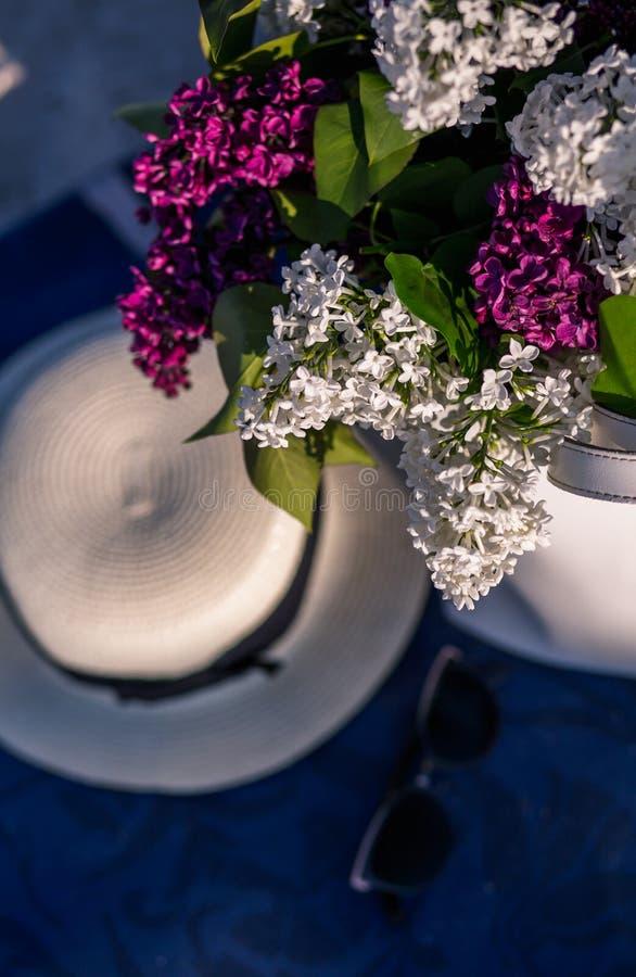 Sombrero del verano de las mujeres con una cinta y un ramo de flores de la lila en un fondo azul Visi?n superior Endecha plana foto de archivo libre de regalías