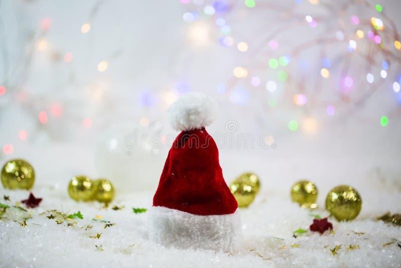 Sombrero en la nieve, fondo que brilla de Santa Claus con las estrellas fotos de archivo libres de regalías