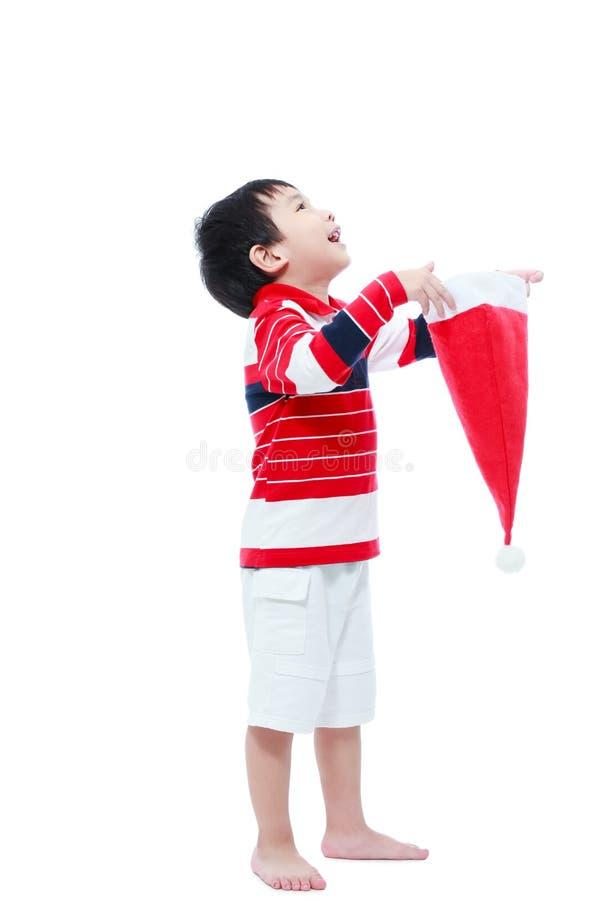 Sombrero feliz de santa del control del muchacho en el fondo blanco imagenes de archivo