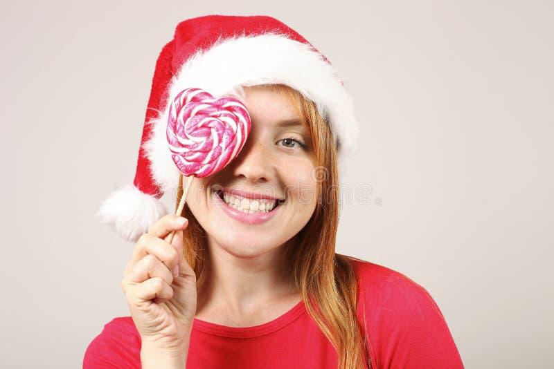 Sombrero femenino del ` s de Papá Noel del pelirrojo que lleva magnífico con el estallido-pom, celebrando días de fiesta festivos fotos de archivo
