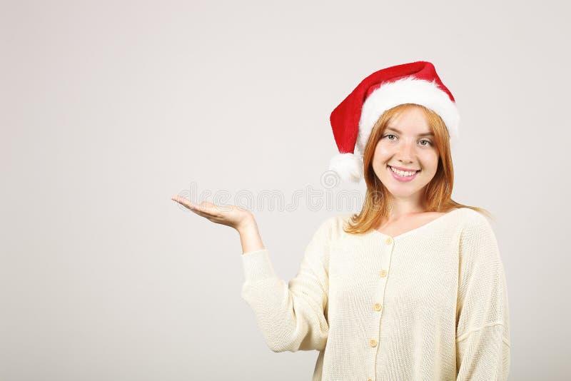 Sombrero femenino del ` s de Papá Noel del pelirrojo que lleva magnífico con el estallido-pom, celebrando días de fiesta festivos imagenes de archivo