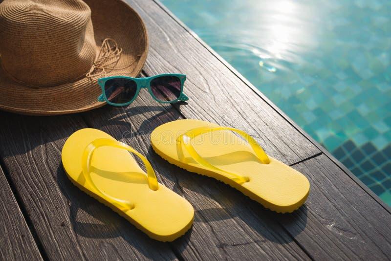 Sombrero, gafas de sol y chancletas por la piscina foto de archivo libre de regalías