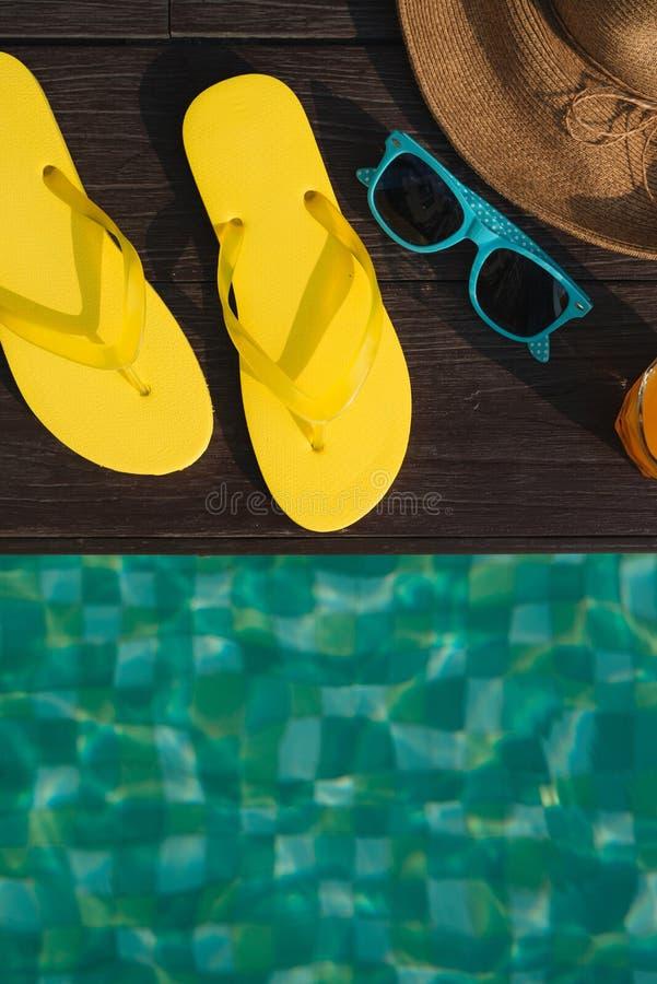 Sombrero, gafas de sol y chancletas por la piscina fotos de archivo libres de regalías