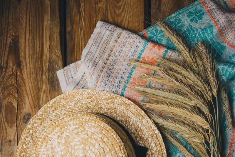 Sombrero hermoso del verano con las espiguillas en fondo de madera en un cierre de la toalla para arriba foto de archivo libre de regalías