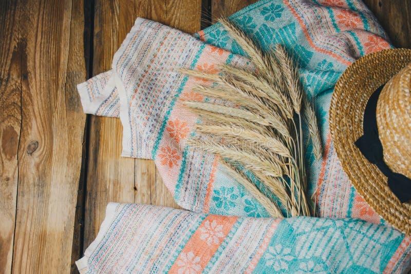 Sombrero hermoso del verano con las espiguillas en fondo de madera en un cierre de la toalla para arriba fotos de archivo libres de regalías