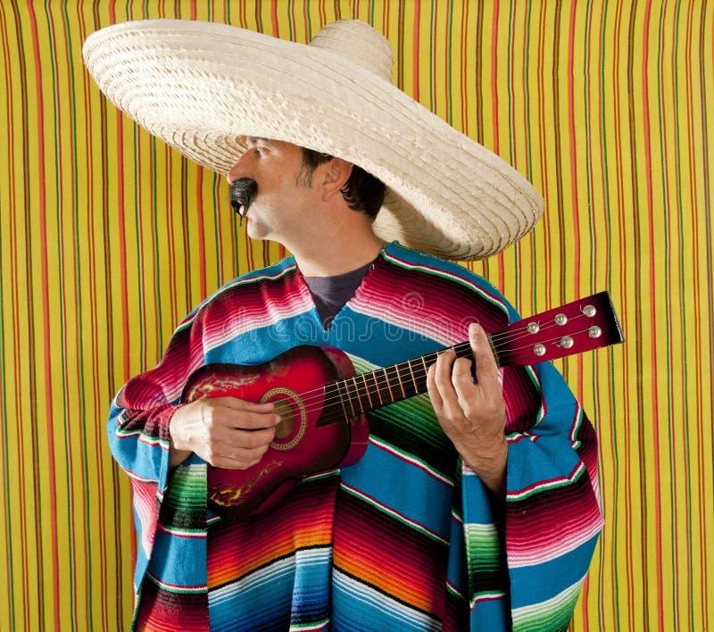 Sombrero messicano del poncio del serape dell'uomo che gioca chitarra fotografia stock libera da diritti