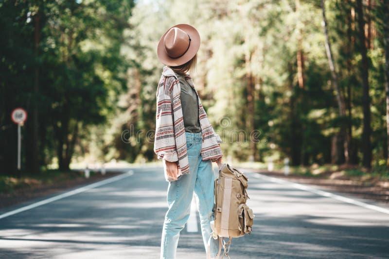 Sombrero que lleva de la mujer hermosa joven del inconformista y mochila y soporte que viajan en el camino foto de archivo