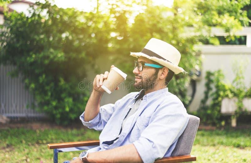 Sombrero que lleva del hombre caucásico, vidrios que beben el café y que se sientan en silla en al aire libre, feliz y sonriendo, imágenes de archivo libres de regalías