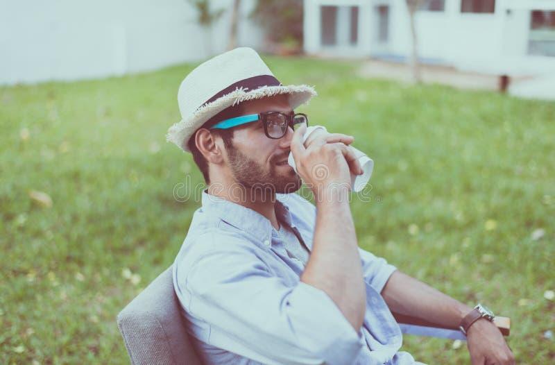 Sombrero que lleva del hombre caucásico, vidrios que beben el café y que se sientan en silla en al aire libre, feliz y sonriendo, foto de archivo
