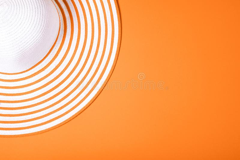 Sombrero rayado de la paja en fondo coralino de vida del color Visi?n superior Endecha plana imagen de archivo libre de regalías