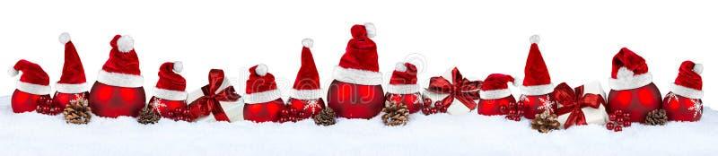 Sombrero rojo de santa de la fila de la chuchería de la Navidad imagenes de archivo