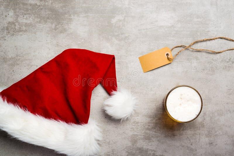 Sombrero rojo de santa y un vidrio de cerveza en una tabla concreta imagenes de archivo